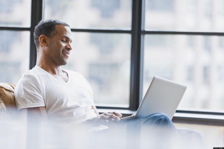 Smiling Man Looking at Laptop in Lap